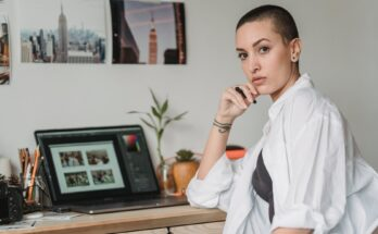 thoughtful woman with stylus working with photos on laptop