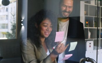 multiethnic cheerful colleagues looking at stickers and smiling