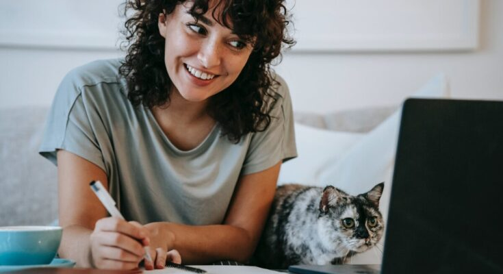 glad woman with cat writing in planner while using laptop