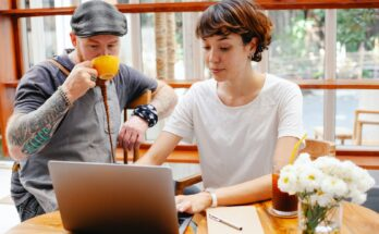 young woman using laptop while man in cap drinking coffee