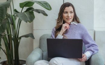 positive young woman working on netbook sitting in armchair in office