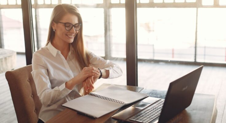 smiling young female entrepreneur checking time on wristwatch while working on laptop in modern workspace