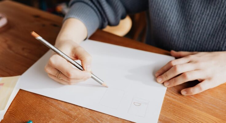crop female designer drawing on paper sheet