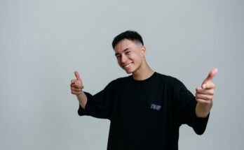 man in a black crew neck shirt pointing his fingers at the camera