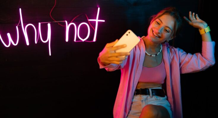 woman in pink cardigan holding smartphone