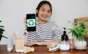 asian woman showing recycling symbol on smartphone